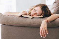 Müder entspannter Frauenschlaf mit Buch auf Sofa lizenzfreie stockfotos