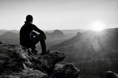 Müder erwachsener Wanderer in der schwarzen Hose, Jacke und dunkle Kappe sitzen auf Klippenrand und dem Schauen zum bunten Nebel  lizenzfreie stockfotografie