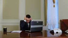 Müder Geschäftsmann beendet, an Laptop zu arbeiten, Arme im Büro sich zu entspannen und auszudehnen stock video footage