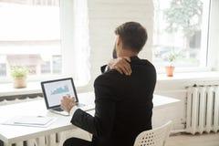 Müder Geschäftsmann, der am Arbeitsplatz nach der Arbeit erschöpft ausdehnt lizenzfreies stockbild