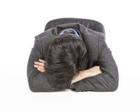 Müder Geschäftsmann, der auf Schreibtisch schläft Lizenzfreies Stockbild