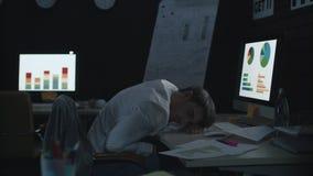 Müder Geschäftsmann, der auf vorderem Computer der Arbeitstabelle im dunklen Büro schläft stock footage