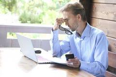 Müder Geschäftsmann in der Freizeitkleidung arbeitet an Laptop dem im Freien Freela Stockfoto