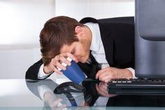 Müder Geschäftsmann, der Kaffeetasse am Schreibtisch hält Lizenzfreie Stockbilder