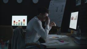 Müder Geschäftsmann, der Kopf beim Anayzing Daten und Finanzdiagramme berührt stock footage