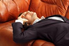 Müder Geschäftsmann mit dem Telefon, das auf dem Sofa liegt Stockfoto