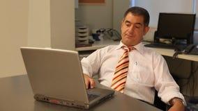 Müder Geschäftsmann unter Verwendung des Laptops im Büro stock video