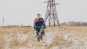 Müder Instandsetzer, der auf das Winterfeld mit elektrischer Station geht stock footage