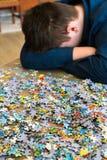Müder Jugendlicher sitzt, seinen Kopf nahe bei Puzzlespielen kippend Stockfotografie