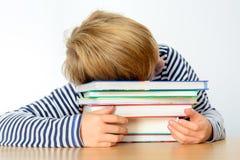 Müder Junge auf einem Stapel von Büchern Stockbild