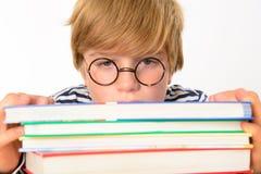 Müder Junge auf einem Stapel von Büchern Lizenzfreies Stockbild