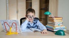 Müder Junge in den lustigen Gläsern, die Hausarbeit tun Kind mit Lernenschwierigkeiten Junge, der Probleme mit seiner Hausarbeit  Stockfoto