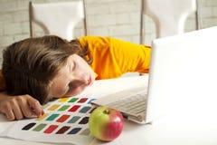 Müder Junge, der auf einer Lektion schläft lizenzfreie stockfotos