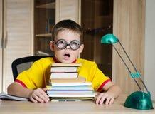 Müder Junge, der die lustigen Gläser tun Hausarbeit trägt Kind mit Lernenschwierigkeiten Junge, der Probleme mit seiner Hausarbei Stockfotografie