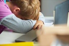 Müder Junge, der im Schlafzimmer studiert Lizenzfreies Stockfoto