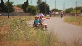 Müder Junge und Mädchen, die an der Straße per Anhalter fährt stock video footage