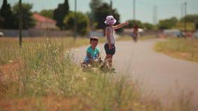 Müder Junge und Mädchen, die an der Straße per Anhalter fährt stock video