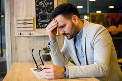 Müder junger Geschäftsmann auf einem Bruch in der Kaffeestube lizenzfreie stockbilder