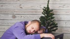 Müder junger Geschäftsmann im Büro auf Sylvesterabend Weihnachtsbaum im Büro Laptop auf Schreibtisch Die goldene Taste oder Errei stock footage