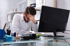 Müder junger Geschäftsmann Sitting In Office lizenzfreie stockbilder