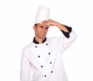 Müder junger männlicher Koch, der mit Kopfschmerzen steht Stockfotografie