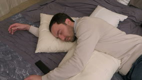 Müder junger Mann liegt auf Bett und schläft nach hartem Arbeitstag ein stock video