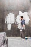 Müder junger Mann mit Farbenrolle nach Hause erneuernd stockbilder