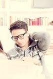 Müder junger Mann mit Gläsern ein Buch lesend Lizenzfreies Stockfoto