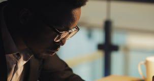Müder junger schwarzer Geschäftsmann, der auf Laptop-Computer schreibt Er arbeitend im Nachtbüro steadicam Schuss stock video