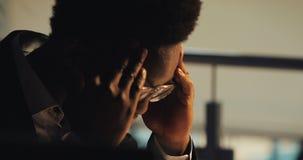 Müder junger schwarzer Geschäftsmann, der mit Dokumenten im Nachtbüro arbeitet Portr?t des h?bschen Gesch?ftsmannes, der Papiere  stock video footage