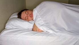 müder Kerl in einem Bett stockfotografie