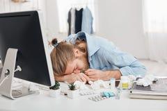 Müder kranker blonder Mann, leiden unter Kopfschmerzen und hoher Temperatur und halten Haupt auf den Händen und sitzen vor Lizenzfreies Stockbild