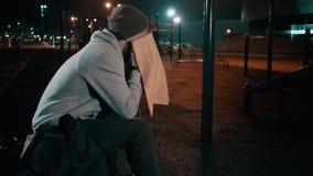 Müder männlicher Athlet wischt sein Gesicht durch Turm auf Sportplatz im Freien in der Nacht ab stock footage
