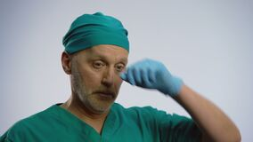 Müder männlicher Doktor, der tief, die medizinische Gesichtsmaske entfernend seufzt und wischen seine Braue stock video footage