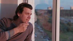 Müder Mann betrachtet heraus das Fenster, das auf dem Balkon Sonnenuntergang am Abend sitzt stock video footage