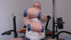 Müder Mann, der Übung mit zwei kleinen Dummköpfen tut stock video footage