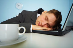 Müder Mann, der auf einem Notizbuch schläft Stockbilder