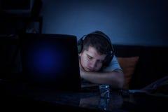 Müder Mann, der hinter dem Laptop wegen des Burnout schläft Stockfoto