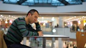 Müder Mann, der im Einkaufszentrum und im Café schläft stock footage
