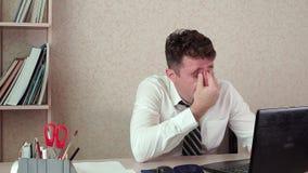 Müder Mann des Bürovorstehers, der an einem Laptop arbeitet stock video