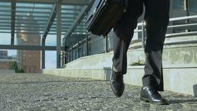 Müder Mann mit Aktenkoffer langsam draußen gehend, Ende des Arbeitstages, overhours stock footage
