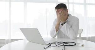 Müder Manndoktor arbeitet an einem Laptop in der Klinik stock video