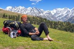 Müder Mannreisender entspannte sich und lag auf der Alpenwiese lizenzfreies stockfoto