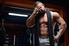 Müder muskulöser Mann an der Turnhalle nach Training lizenzfreie stockfotos