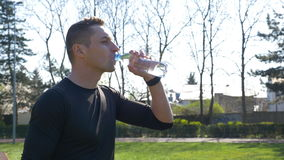Müder Rüttler in Trinkwasser der Sportkleidung von der Plastikflasche nach Marathon stock footage