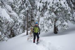 Müder Reisender, in den Schneeschuhen, schleppt ein Arm voll Brennholz stockfoto