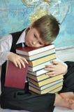 Müder Schüler mit einem Stapel der Bücher Stockbilder