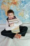 Müder Schüler mit einem Stapel der Bücher Stockfotografie