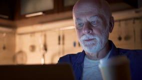 Müder schläfriger älterer Geschäftsmanngebrauchslaptop am Hausbüro Müder Manngetränkkaffee von der Papierschale stock video footage