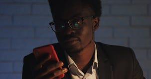 Müder schläfriger Büroangestellter unter Verwendung des Smartphone im Nachtbüro Geschäftsmann versucht sich zu konzentrieren stock video footage